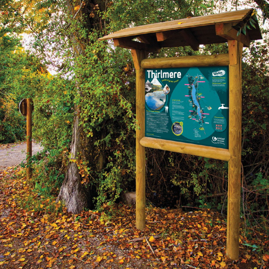 Information sign in wooden frame, with sloped roof – positioned in wooded area next to pathway.